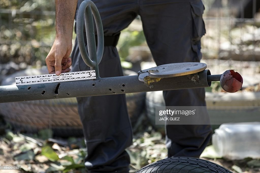 Israeli bomb disposal expert sets a ruler as another expert takes photos of the damage caused by a rocket, fired by Palestinian militants from the Gaza Strip, after it landed in the courtyard of a kindergarten in the southern costal Israeli city of Ashdod, on August 26, 2014. Israel upped the pressure on Hamas, with warplanes hitting two Gaza City highrises on day 50 of their conflict as the warring parties mulled a new Egyptian truce proposal.