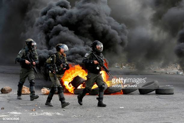 TOPSHOT Israeli border guards advance down a street during clashes with Palestinian protesters following a demonstration in the West Bank city of...