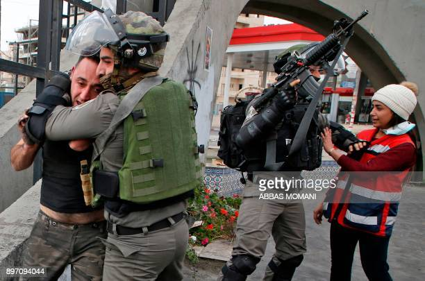 Israeli border guards detain a Palestinian man during clashes with Palestinian protesters north of Ramallah in the Israeli occupied West Bank on...