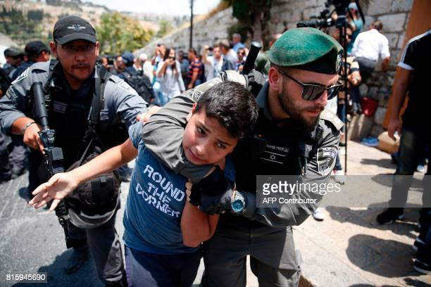 TOPSHOT Israeli border guards detain a Palestinian youth during a demonstration outside the Lions Gate a main entrance to AlAqsa mosque compound due...