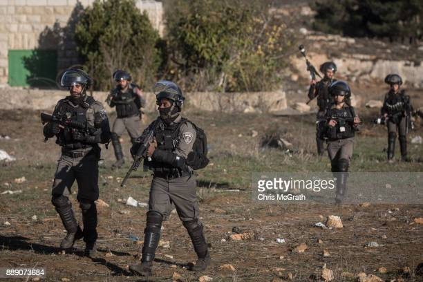 Israeli border guards fire tear gas at Palestinian protesters during clashes near an Israeli checkpoint on December 9 2017 in Ramallah West Bank...