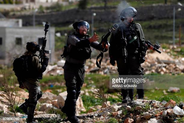 TOPSHOT Israeli border guards fire teargas canisters towards Palestinian protesters following a demonstration in the West Bank city of Ramallah on...