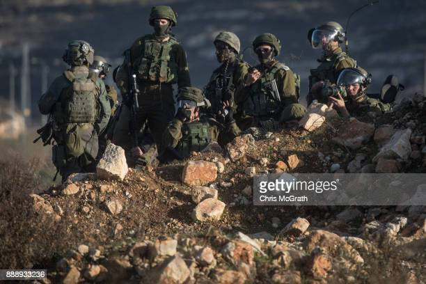 Israeli border guards hold a position during clashes with Palestinian protesters near an Israeli checkpoint on December 9 2017 in Ramallah West Bank...