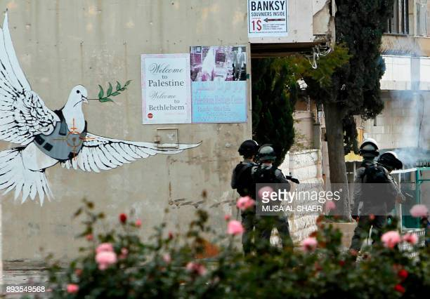 Israeli border guards hold a position next to a mural during clashes with Palestinian protestors following a demonstration in Bethlehem in the...