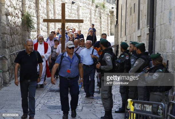 Israeli border guards keep watch as a group of Christian pilgrims walk in the Via Dolorosa in Jerusalem's old city on July 28 2017 Palestinians held...