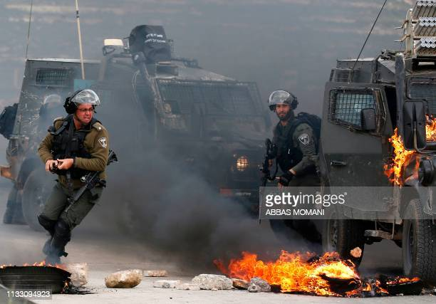 TOPSHOT Israeli border guards move away from a burning military vehicle during clashes with Palestinian demonstrators who took to the streets on the...