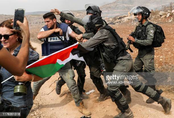 TOPSHOT Israeli border guards scuffle with a photojournalist as a woman holding up a Palestinian flag passes through amidst clashes with Palestinian...