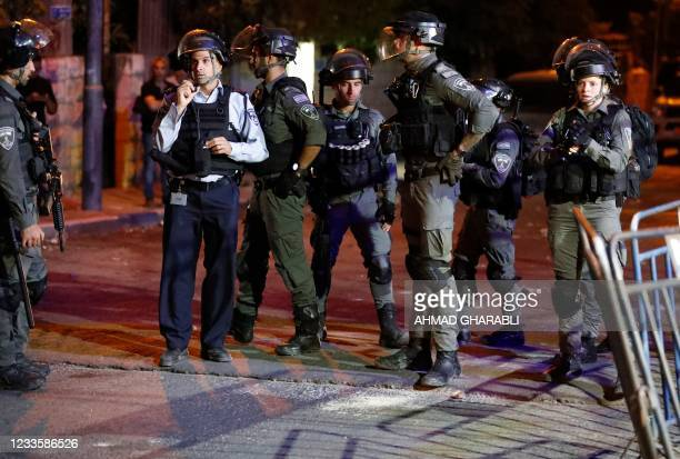 Israeli border guards stand at attention in the east Jerusalem neighbourhood of Sheikh Jarrah on June 21 during clashes between Israeli far-right...