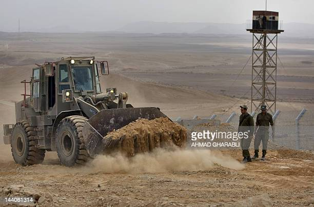 Israeli border guards supervise as a bulldozer moves dirt at the construction site of a border fence along Israel's border with Egypt near the Red...