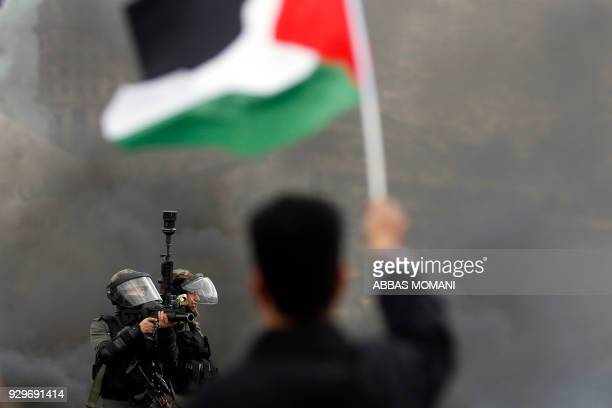 TOPSHOT Israeli border guards take aim as a Palestinian protester waves the national flag during clashes following a demonstration in the West Bank...