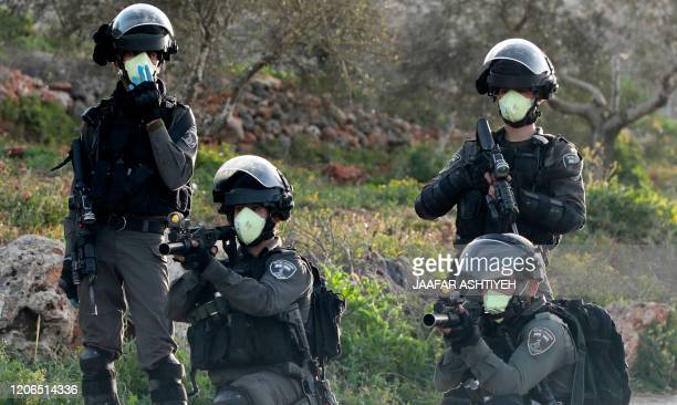 Israeli border guards wearing protective masks aim their weapon during clashes with Palestinian youths in a village south of Nablus in the occupied...
