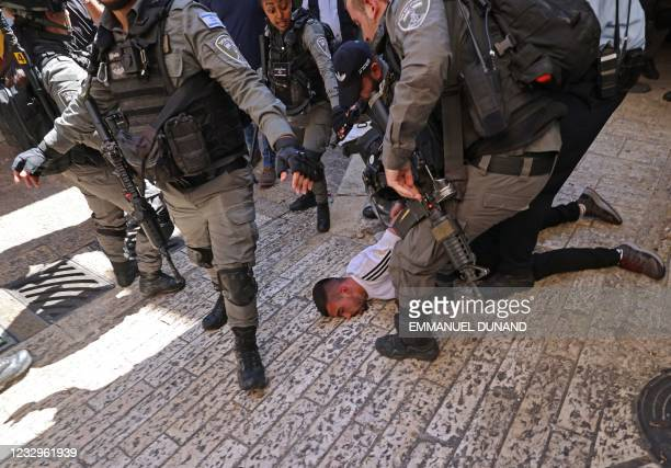 Israeli border police detain a Palestinian man during protests against Israel's occupation and its air campaign on the Gaza strip, at Damascus Gate...
