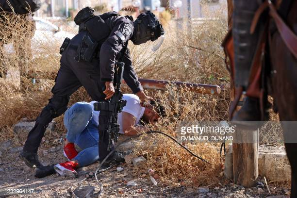 Israeli border police detain a Palestinian man during protests against Israel's occupation and its air campaign on the Gaza strip, at the flashpoint...