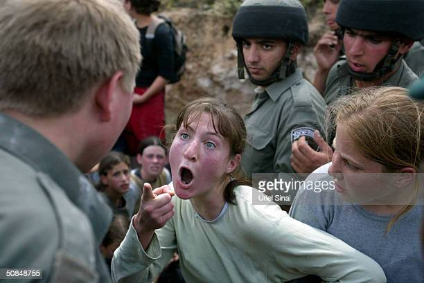 Israeli border police officers evacuate Jewish settlers by force May 17, 2004 in the West Bank outpost of Mitzpe Yizhar, near Nablus. According to...