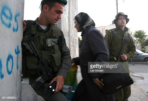 Israeli border police officers look at a Palestinian woman as she walks through a section of Israel's separation barrier in the west bank village of...