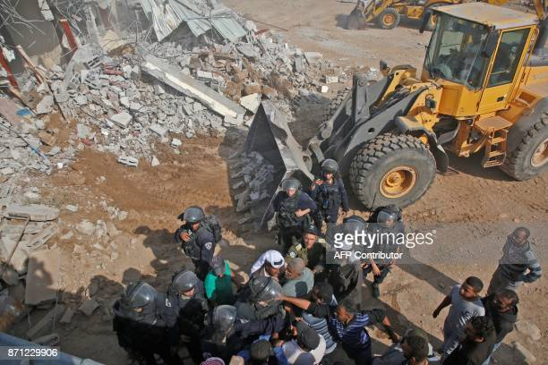 Israeli border police scuffle with Palestinians as an Israeli army bulldozer demolishes a Palestinian house that was reportedly built without...