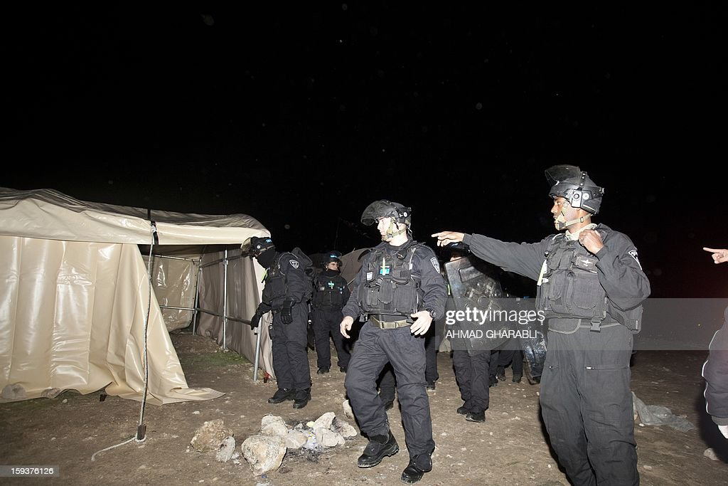 Israeli border police search an outpost of tents as they prepare to evacuate Palestinian protesters from the scene in the controversial West Bank area known as E1 between Israeli annexed east Jerusalem and the settlement of Maaleh Adumim early on January 13, 2013. Israeli police early on January 13 evicted Palestinian protesters from a hilltop camp they set up in a West Bank area slated for Jewish settlement, police and witnesses said.