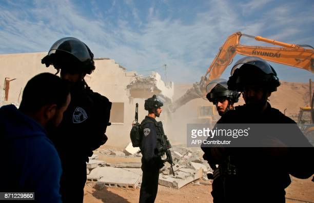 Israeli border police stand guard as an Israeli army bulldozer demolishes a Palestinian house that was reportedly built without permission in the...