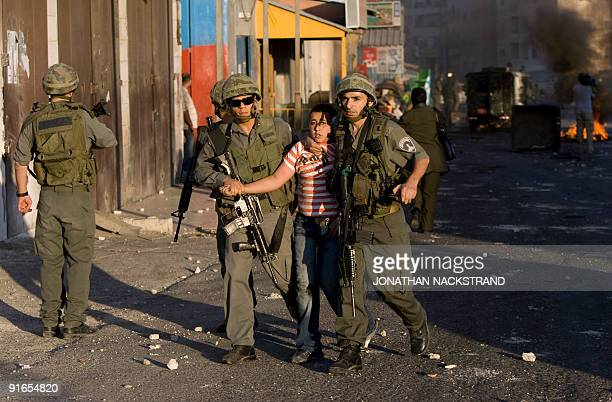 Israeli border policemen detain a Palestinian stonethrowing youth during clashes on October 5 2009 in the east Jerusalem Shuafat refugee camp Police...