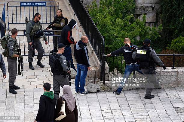Israeli border policemen frisk Palestinian men at Damascus Gate in the Old city of Jerusalem on March 18 2016 / AFP / AHMAD GHARABLI