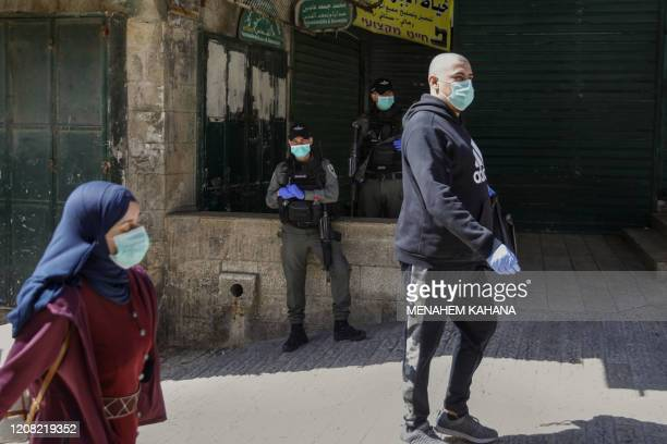 Israeli border policemen look on as Palestinians walk by all wearing protective masks amid the COVID19 outbreak in Jerusalem's Old City on March 25...