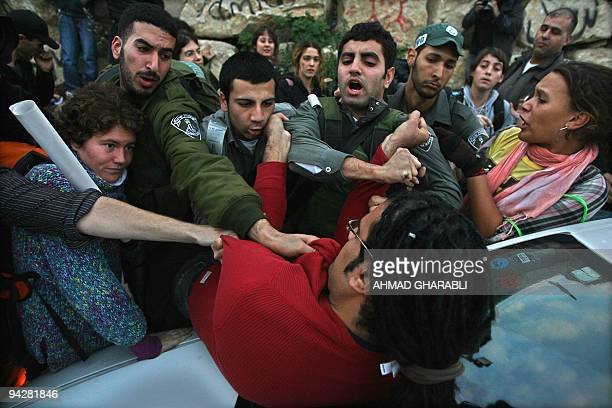 Israeli border policemen scuffle with an Israeli peace activist during a demonstration against the eviction of the Palestinian Kurd family from their...