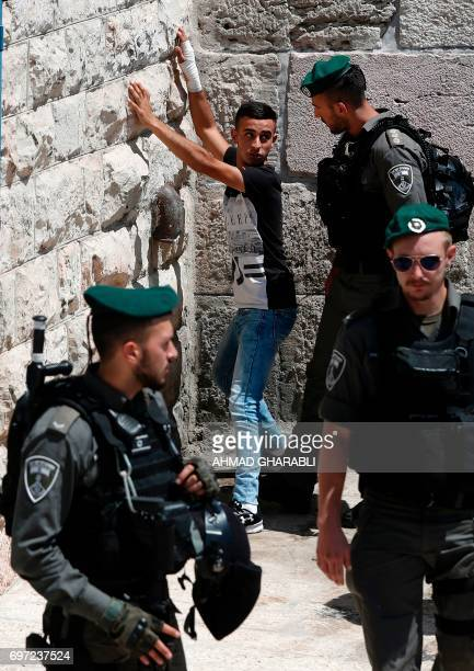 Israeli borderguards frisk a Palestinian man outside Damascus Gate in Jerusalem's Old City on June 18 2017 / AFP PHOTO / AHMAD GHARABLI
