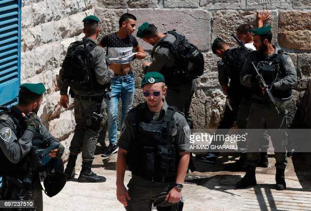 Israeli borderguards frisk Palestinian men outside Damascus Gate in Jerusalem's Old City on June 18 2017 / AFP PHOTO / AHMAD GHARABLI