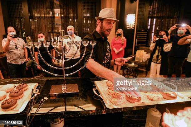 Israeli businessman Gil Gurevitch chants religious hymns as he lights a Hanukkah menorah at a hotel in Dubai where Israeli entrepreneurs are...