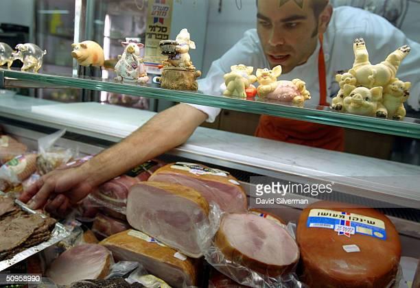 Israeli butcher Ronen Solomon arranges a display of nonkosher meats in his delicatessen June 14 2004 in Ranana in central Israel Israel's High Court...