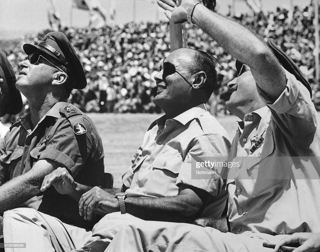 Israeli chiefs watch an air show over the Negev Brigade Monument in celebration of Israel's military victory in the 6-Day War with Egypt, Jordan, and Syria. From left to right are; Chief of Staff Itzhak Rabin, Defense Minister Moshe Dayan, and Chief of the Israeli Air Force Mordechai Hod. | Location: Israel Southern District, Israel.