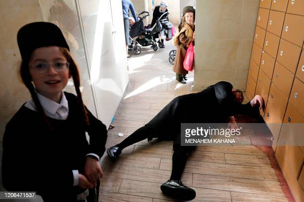 Israeli children check at an ultraOrthodox Jewish man lying drunk on the floor in the central Israeli city of Bnei Brak on March 10 2020 during the...