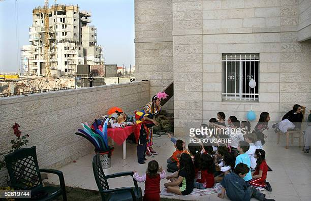 Israeli children enjoy a party as a construction site is seen in the background in the West Bank settlement of Maale Adumin 12 April 2005 President...
