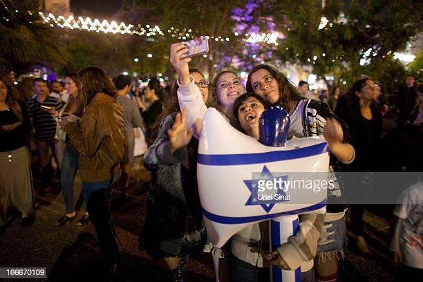 Israeli children get their piture taken as Israelis celebrate the Jewish state's 65th Independence Day on April 15 2013 in Tel Aviv Israel