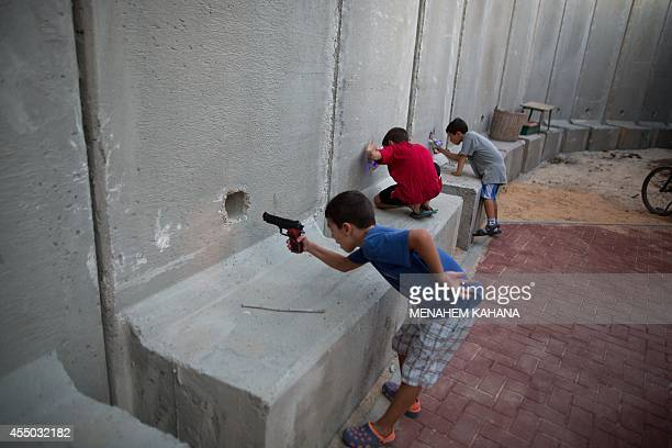 Israeli children hold toy guns as they pretend to play war games next to newly built protection cement walls around a kindergarten in the center of...