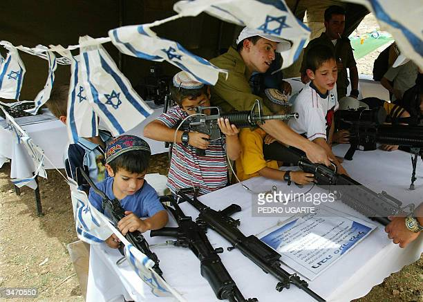 Israeli children play with weapons during an army weapon display to mark the 56th anniversary of Israel's Independence Day in the West Bank...