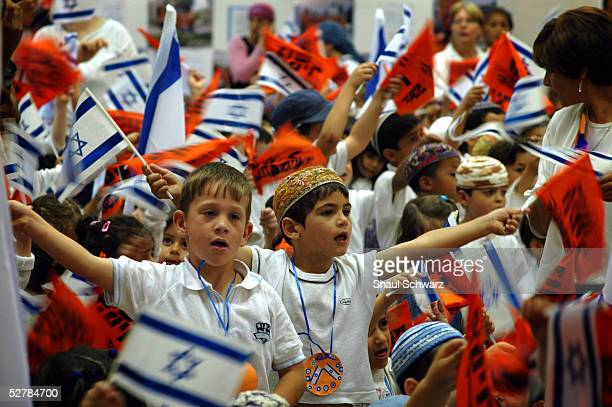 Israeli children wave flags during a rehearsal for an Independence Day ceremony in the Jewish settlement of Neve Dekalim May 9 2005 in the Gaza Strip...
