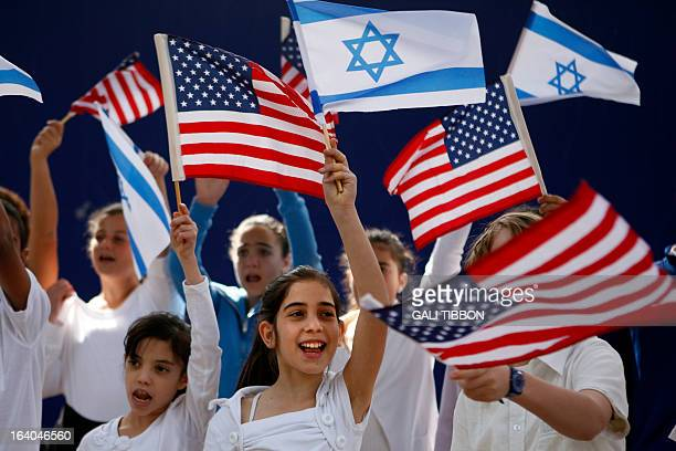 Israeli children wave Israeli and US flags as they sing during a rehearsal at the residence of Israeli President Shimon Peres in Jerusalem on March...