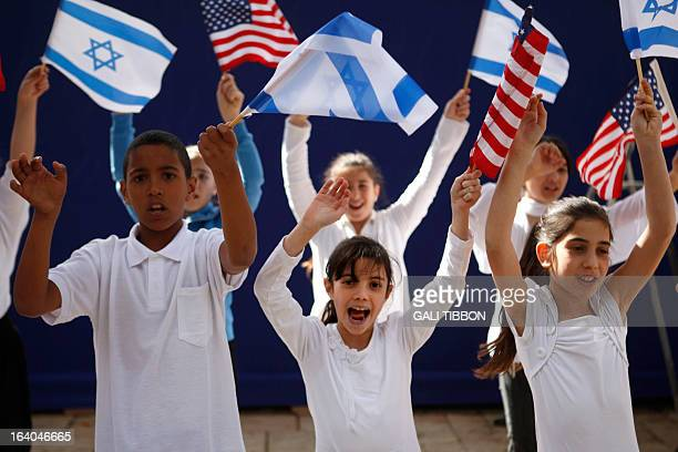 Israeli children wave Israeli and US flags as they sing during a rehearsal at the residence of President Shimon Peres in Jerusalem on March 19 a day...
