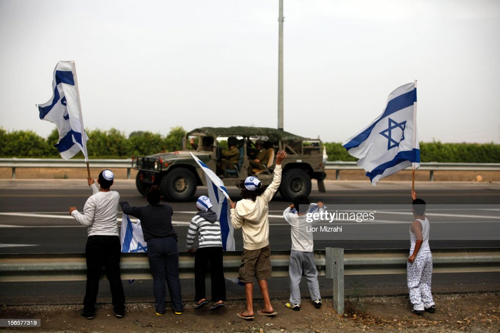 Israeli children wave their national flag as they greet an army convoy passing on a road leading to the Israel-Gaza border near the southern Israeli town of Ofakim on November 17, 2012 in Israel. At least 39 Palestinians and three Isreali's have died since conflict began four days ago. Israeli troops have been massing on the border as some 200 targets were hit overnight in Gaza, including Hamas cabinet buildings.