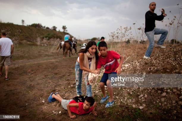 Israeli civilians run for cover during a rocket attack launched from from Gaza on November 17 2012 in Tel Aviv Israel At least 39 Palestinians and...