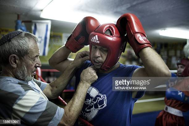 Israeli coach Gershon Luxembourg fixes the head protection of a Palestinian boxer as he trains with Israelis at a boxing club that encourages...