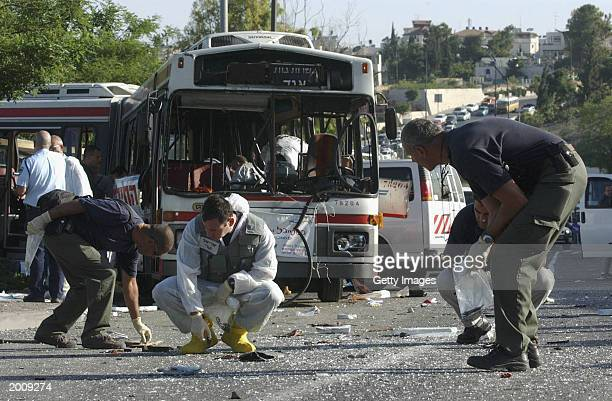 Israeli crime scene investigators pick up evidence May 18 2003 after a Palestinian suicide bomber exploded himself on an early morning passenger bus...