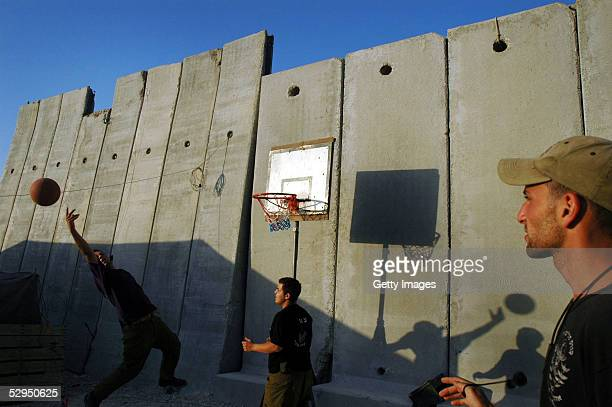 Israeli Defense Forces soliders play basketball behind a barrier wall before a night patrol May 18 2005 in Gush Katif Gaza strip Tension has grown...