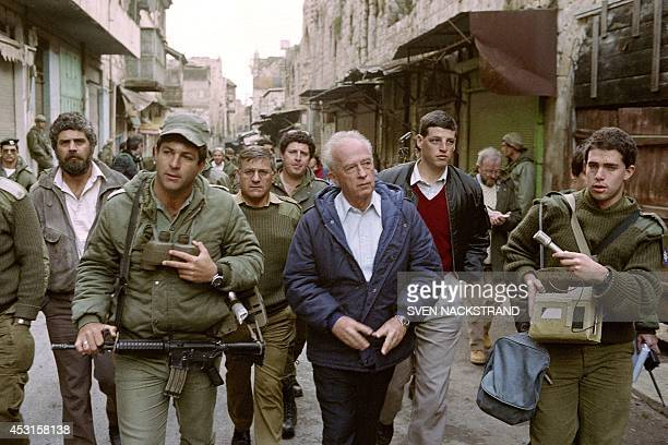 Israeli Defense Minister Yitzhak Rabin walks on February 3, 1988 in the old city of Nablus with an Israeli soldier during his West Bank tour. Nablus...