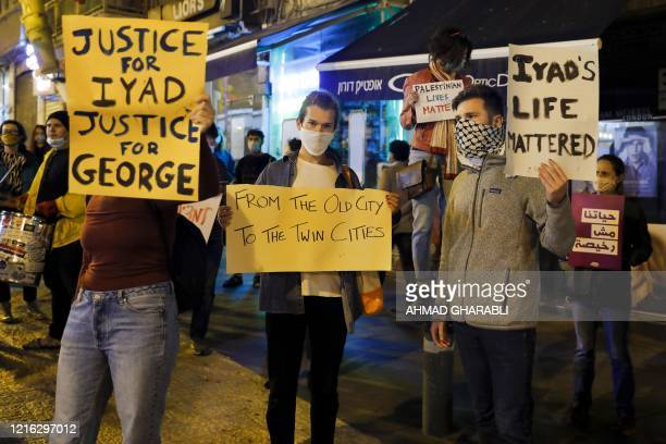 Israeli demonstrators carry placards during a demonstration condemning the shooting of Iyad Hallak a disabled Palestinian man who was shot dead by...