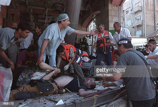 Israeli doctors and medics tend to the injured at the site of a Palestinian suicide bombing August 9 2001 in Jerusalem Israel At least 18 people...