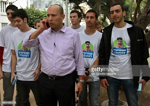 Israeli Economy Minister and head of the farright Jewish Home party Naftali Bennett speaks on the phone as he meets citizens in the streets of the...