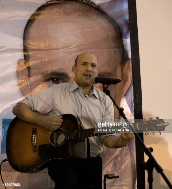 Israeli Economy Minister and head of the rightwing Jewish Home party Naftali Bennett plays the guitar and sings during an election campaign gathering...