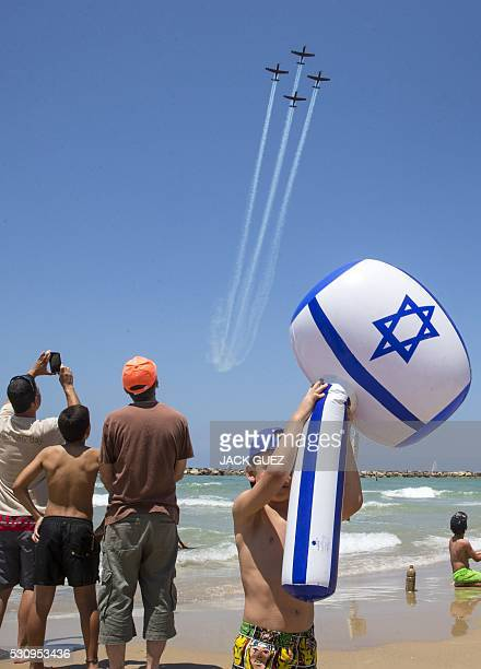 Israeli Efroni T6 Texan II planes perform during an air show over the beach in the coastal city of Tel Aviv on May 12 2016 as Israel marks...
